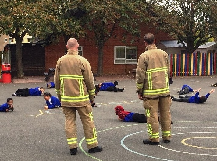 Firefighters teaching children to stop drop and roll